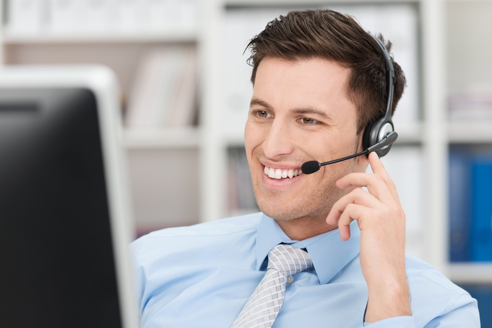 Smiling friendly handsome young male call centre operator or client services personnel beaming as he listens to a call and checks information on his computer monitor.jpeg